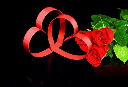 St. Valentine Day. Intertwining of two hearts, on black background with red roses. photo