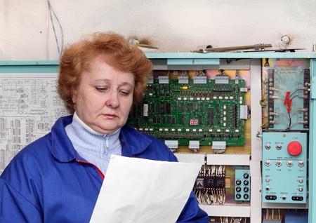 Operator woman-engineer in machine room (elevator) near electronic cabinet. photo