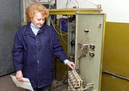 Operator woman-engineer in machine room (elevator) check the mechanical relay and cabinet. photo