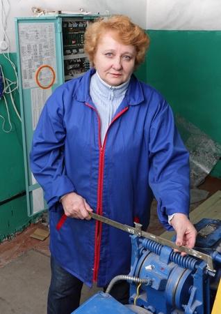 Operator woman-engineer in machine room (elevator) check the mechanical equipment. photo