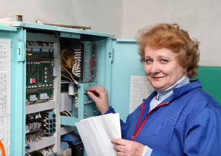 Operator woman-engineer in machine room (elevator) near electronic cabinet. photo