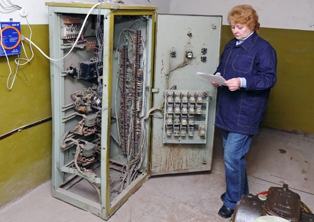 elevator operator: Operator woman-engineer in machine room (elevator) check the mechanical relay and cabinet.