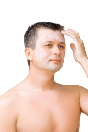 fop: A young man puts on face cream mask . Isolated over white