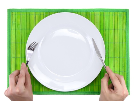 trivet: Hands hold fork and knife above plate on bamboo mat. All around Isolated. Stock Photo