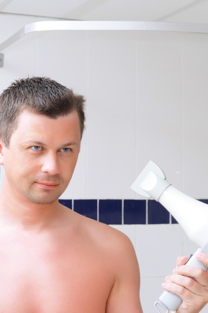 A young man uses a lotion after shaving in bathroom. photo