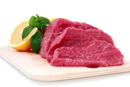 hardboard: Beef steak  on meat hardboard with green leaf and lemon. Isolated.