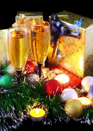 stemware: Christmas and New Year decoration- balls, tinsel, candel and glasses of champagne .On black background.
