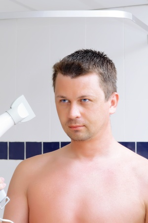 fop: The young man dry a hair in bathroom.