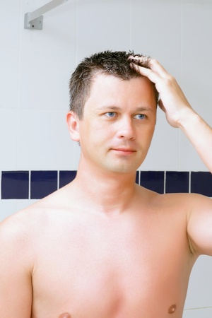 fop: A young man uses a lotion after shaving in bathroom. Stock Photo