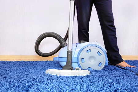 Powelful vacuum cleaner in action-a men cleaner a carpet. Stock Photo - 11854882