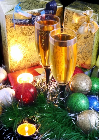 Christmas and New Year decoration- balls, tinsel, candel and glasses of champagne .On black background.