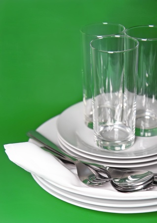 Pile of white plates, glasses with forks and spoons on silk napkin. Green background Stock Photo - 11870932