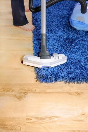 The metal pipe of vacuum cleaner in action -clean a carpet and laminated flooring board. photo