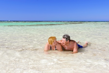 Mature couple on the beach in the tropical resort. photo