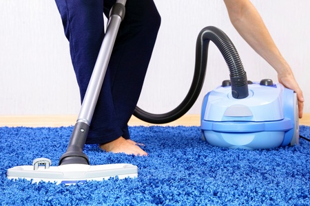 Powelful vacuum cleaner in action-a men cleaner a carpet. photo