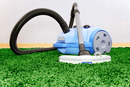 Vacuum cleaner stand  on green  carpet photo