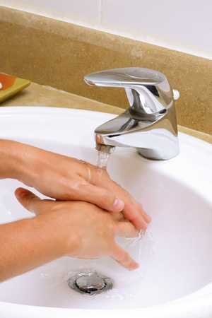 Washing hands before eating in white sink. photo