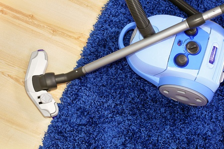 Powerful vacuum cleaner stand  on blue carpet. photo