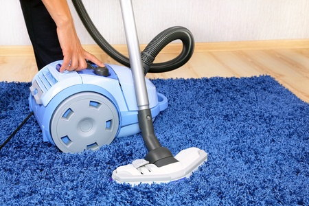 neatness: Powelful vacuum cleaner in action-a men cleaner a carpet.