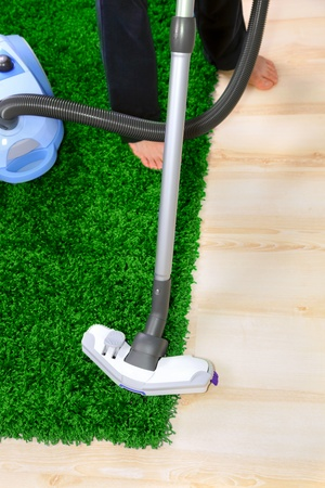 clean carpet: The metal pipe of vacuum cleaner in action -clean a carpet and laminated flooring board.