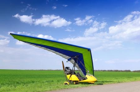 motorizado: Ala delta motorizada sobre la hierba verde, listo para volar.