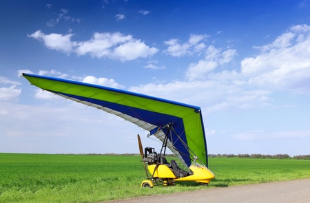 airborne: Motorized hang glider over green grass, ready to fly.