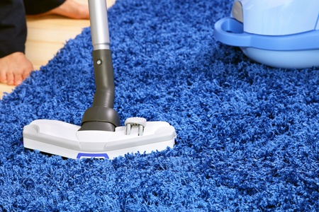 carpet clean: The metal pipe of vacuum cleaner in action -clean a carpet and laminated flooring board.