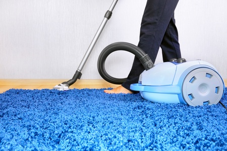 Powelful vacuum cleaner in action-a men cleaner a carpet.