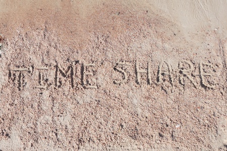"Inscription ""TimeShare"" on a sand n a beach."