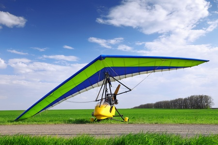motorized: Motorized hang glider over green grass, ready to fly.