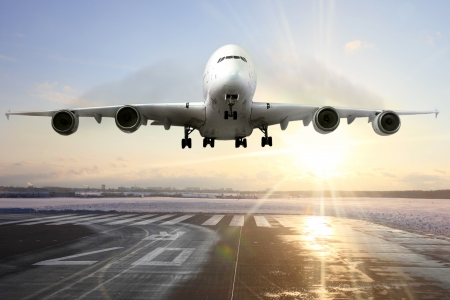 descending: Passenger airplane landing on runway in airport. Evening  Stock Photo