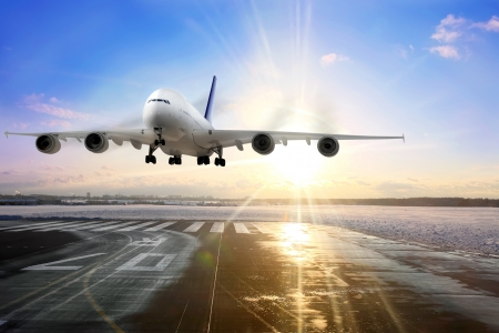 landing: Passenger airplane landing on runway in airport. Evening  Stock Photo