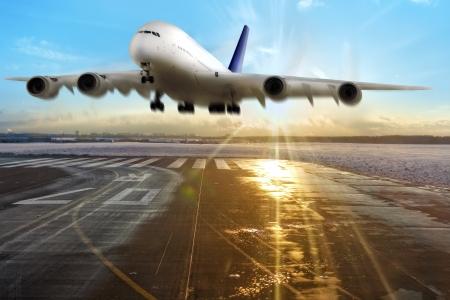 乗客の飛行機の空港の滑走路に着陸します。夕方。