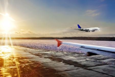 Passenger airplane landing on runway in airport. Evening. photo
