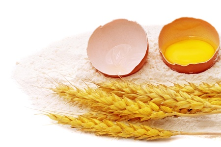 spikelets: Spikelets of wheat with egg on flour spillage.Isolated Stock Photo