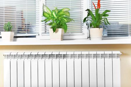 Heating white radiator radiator with flower and window photo