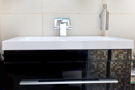White sink and soap dispenser photo