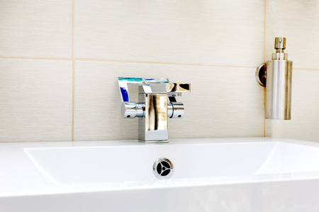 Chromium-plate tap on white sink photo