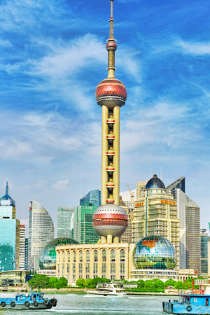 pudong district: SHANGHAI-MAY 24, 2015. Oriental Pearl Tower on  blue sky background. Tower  470 meter the Oriental Pearl is one of Shanghais tallest buildings, located at Lujiazui finance and trade zone in Pudong district in most dynamic city of China. Editorial
