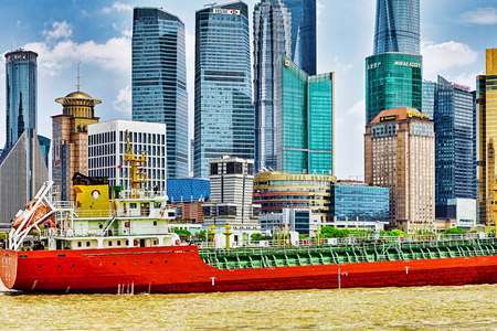 shantytown: SHANGHAI, CHINA-  MAY 24, 2015 : A large cargo ship on the Yangtze River and view on Pudong New Area with skyscrapers and office buildings, Shanghai. China