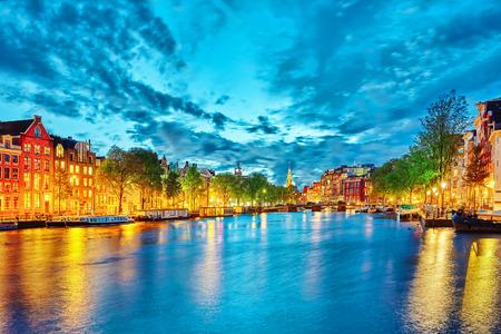Slavný Amstel řeka a noční pohled na krásné město Amsterdam. Nizozemí