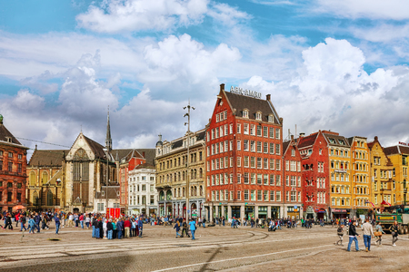 dam square: AMSTERDAM, NETHERLANDS - SEPTEMBER 15, 2015: Beautiful Amsterdam, people in the centre of  Dam Square in the daytime.Square is a central place for local inhabitants and tourists of the Dutch capital. Netherlands