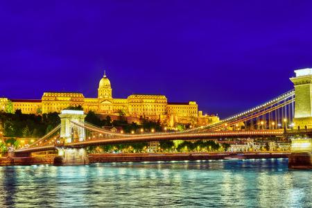 szechenyi: Budapest Royal Castle and Szechenyi Chain Bridge at dusk time from Danube river, Hungary.