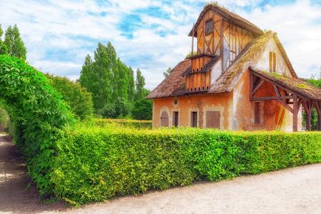 VERSAILEES, FRANCE- JULY 02, 2016 : Landscape of hamlet Queen Marie Antoinettes estate near Versailles Palace. Palace Versailles -most beautiful palace in France. Editorial