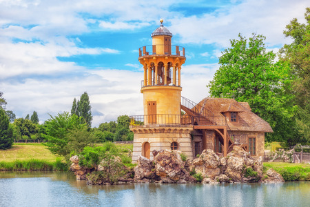 VERSAILEES, FRANCE- JULY 02, 2016 : Lighthouse on the lake in  hamlet Queen Marie Antoinettes estate near Versailles Palace.