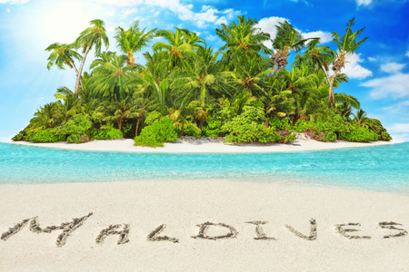 uninhabited: Whole tropical island within atoll in tropical Ocean. Uninhabited and wild subtropical isle with palm trees. Inscription Maldives in the sand on a tropical island,  Maldives.