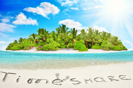 Whole tropical island within atoll in tropical Ocean. Uninhabited and wild subtropical isle with palm trees. Inscription TimeShare in the sand on a tropical island,  Maldives. Stock Photo