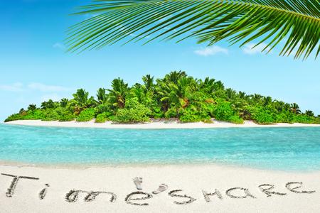 熱帯海洋の環礁内全体の熱帯の島。ヤシの木と野生の無人と亜熱帯島。碑文「タイムシェア」熱帯の島、モルディブの砂の上。 写真素材