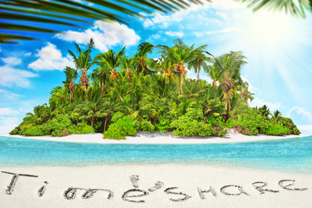 timeshare: Whole tropical island within atoll in tropical Ocean. Uninhabited and wild subtropical isle with palm trees. Inscription TimeShare in the sand on a tropical island,  Maldives. Stock Photo