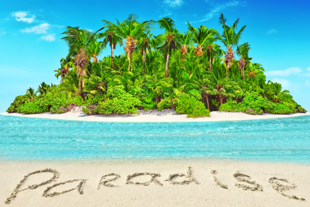 Whole tropical island within atoll in tropical Ocean. Uninhabited and wild subtropical isle with palm trees. Inscription Paradise in the sand on a tropical island.